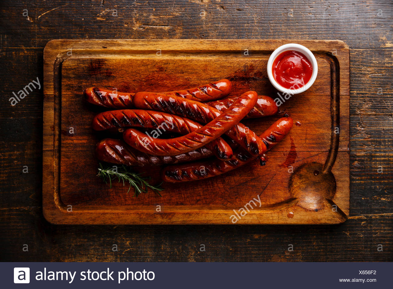 Grilled roasted sausages and ketchup sauce on cutting board on wooden background - Stock Image