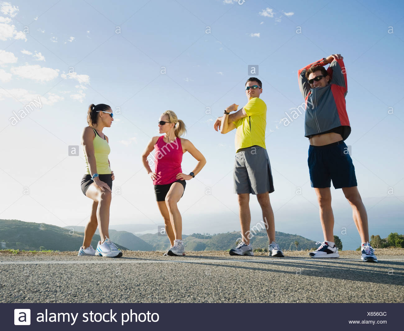Runners stretching on the side of the road - Stock Image
