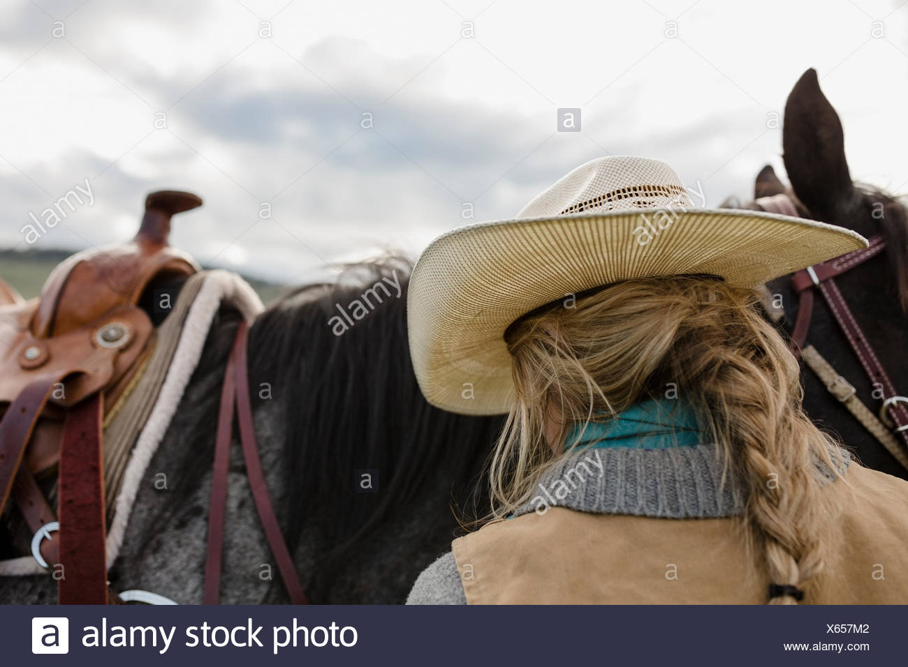 Blonde braided female rancher cowboy hat with horse - Stock Image