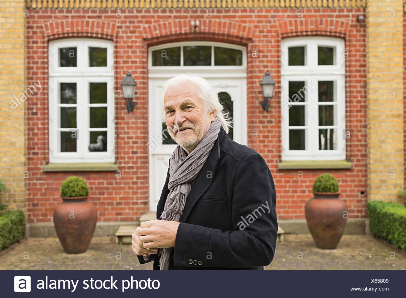 Portrait of senior man wearing jacket and scarf outside house - Stock Image