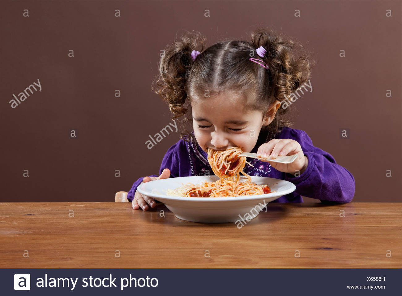 A young girl with her eyes shut tightly eating spaghetti, studio shot - Stock Image
