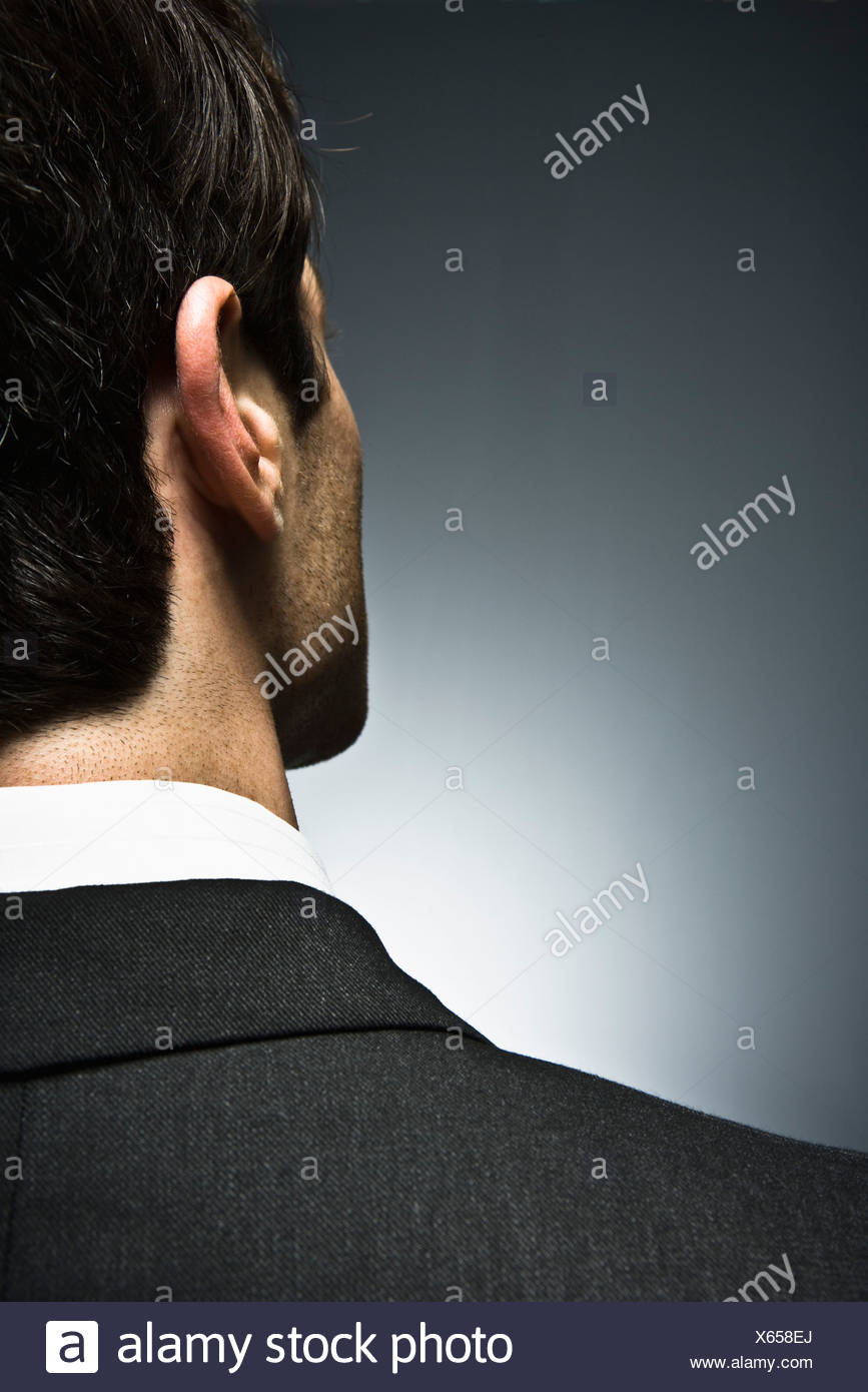 Man looking away with air of uncertainty, rear view - Stock Image