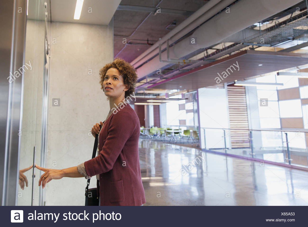 Woman pushing button on elevator at office. - Stock Image