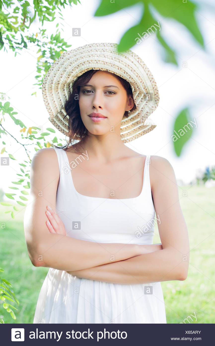 Portrait of confident young woman in sundress and hat standing arms crossed in park - Stock Image