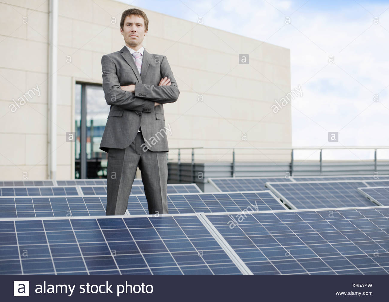 A businessman standing amongst solar panels - Stock Image