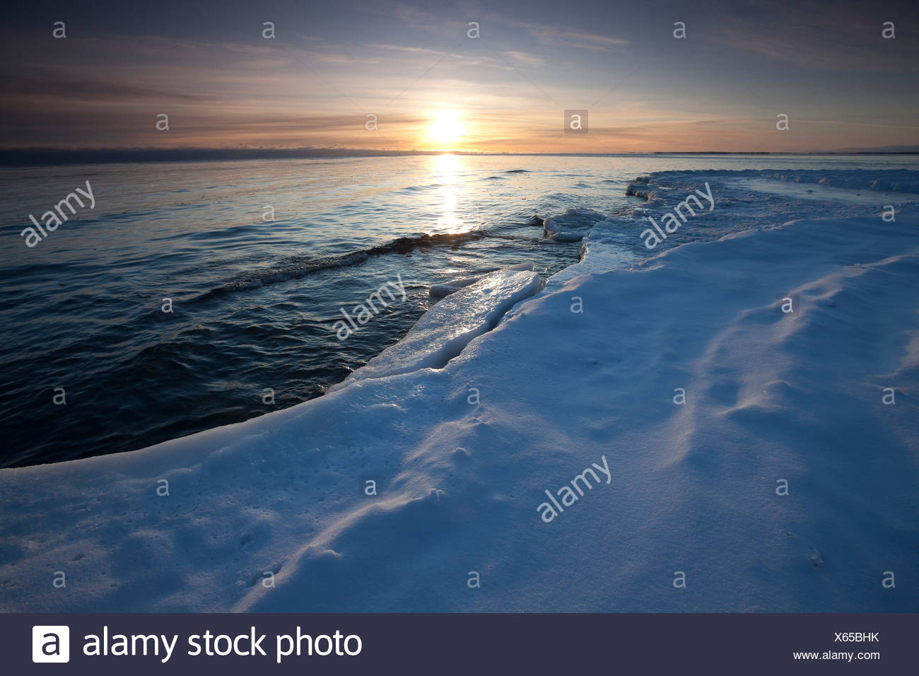 A winter's dawn on the snow covered shores of Lake Ontario in Presqu'ile Provincial Park, Ontario, Canada - Stock Image