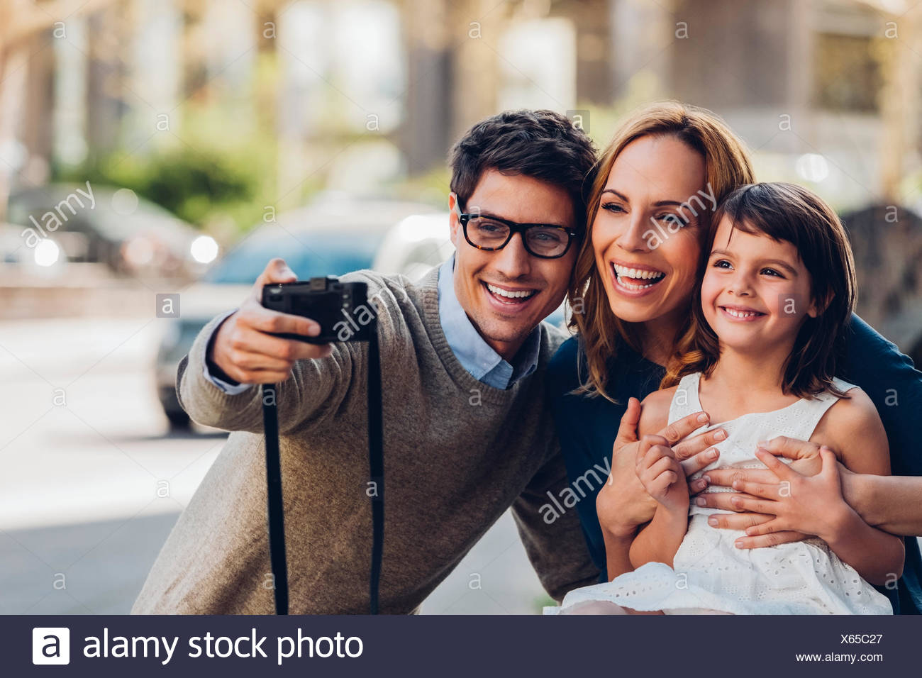 Man outdoors taking a selfie of his family with digital camera - Stock Image