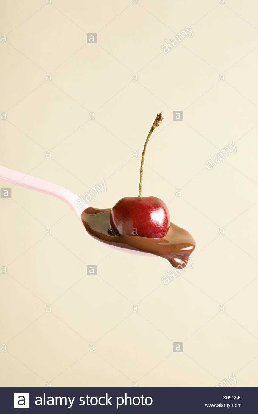 Cherry and melted chocolate on spoon - Stock Image