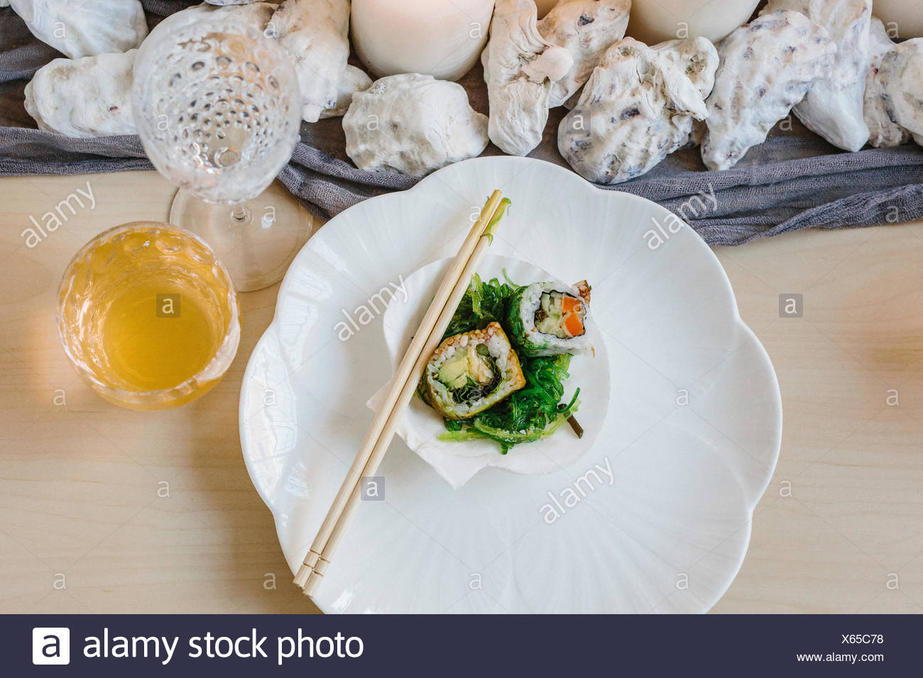 Overhead view of plates of sushi and a table setting for a celebration meal. - Stock Image