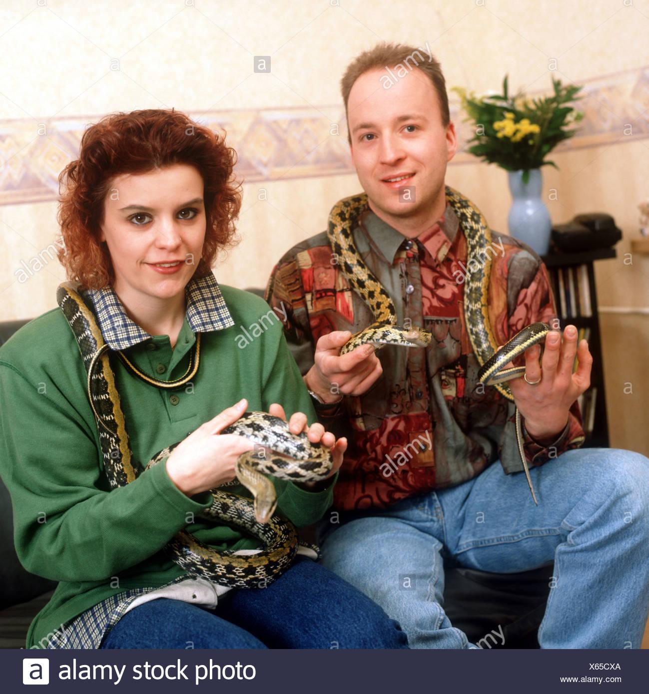 Couple with pet snakes on sofa  - SerieCVS500201b - Stock Image