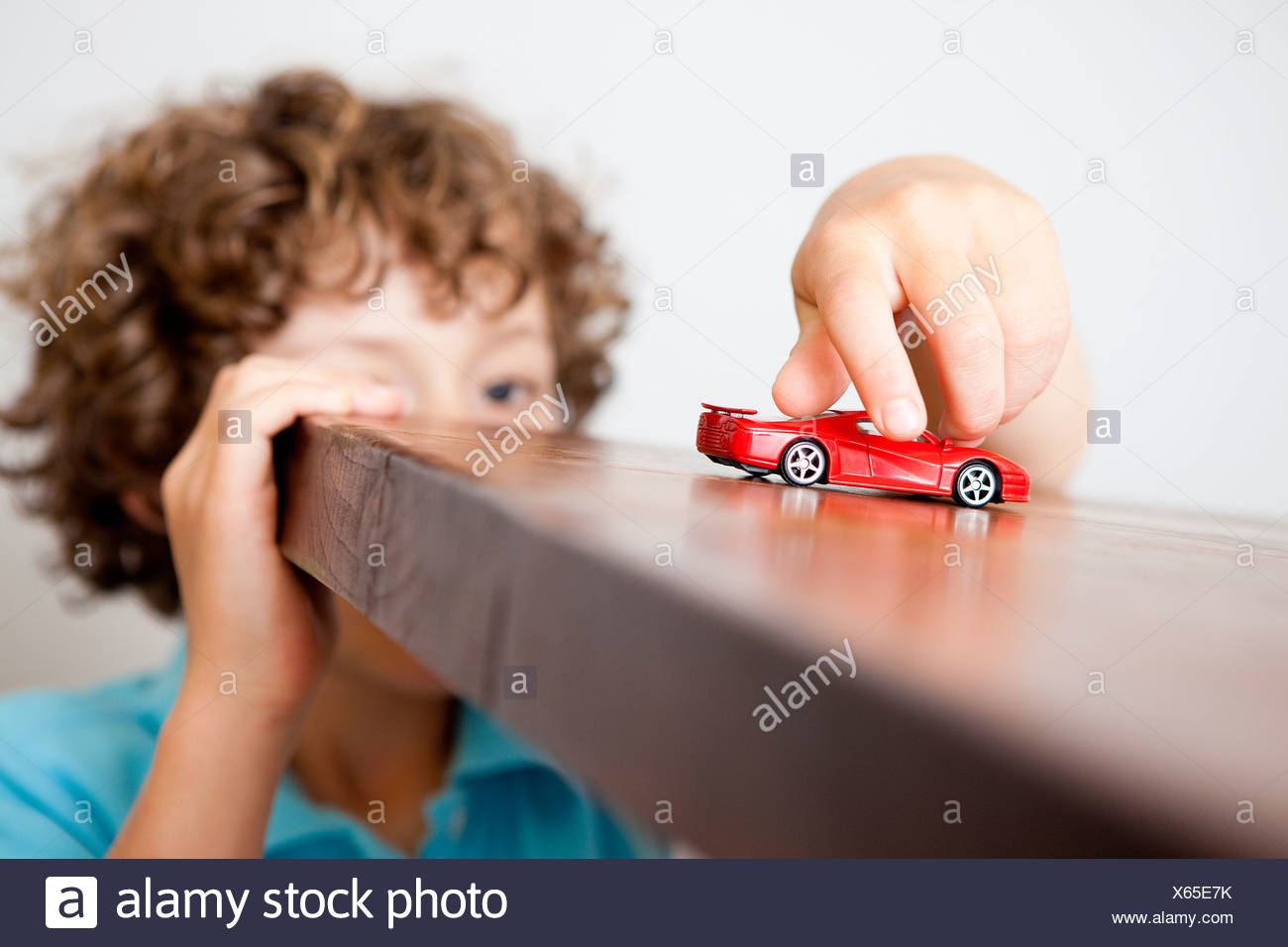 Boy playing with small red car Stock Photo