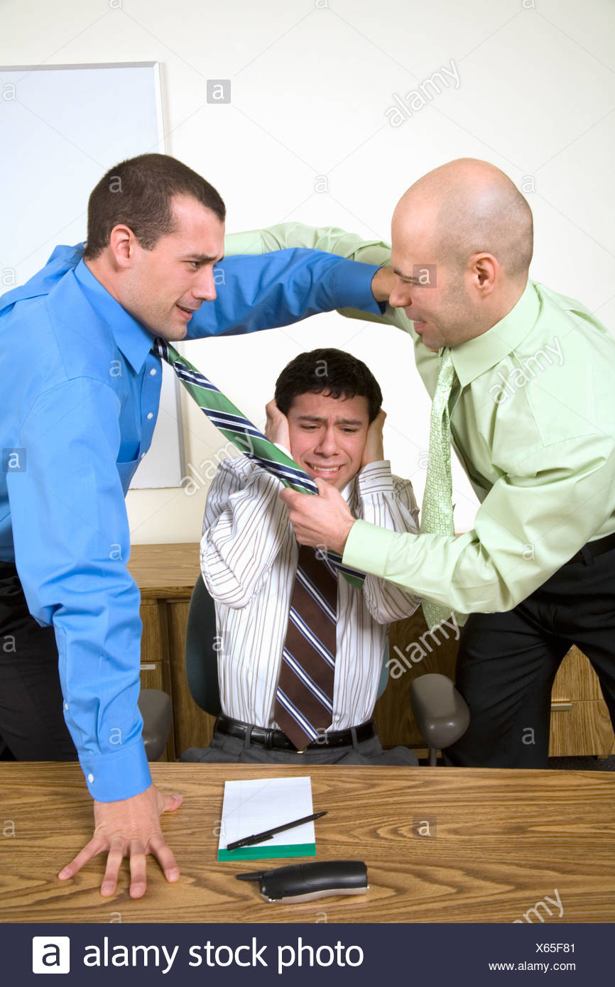 Two businessmen fighting above co-worker - Stock Image