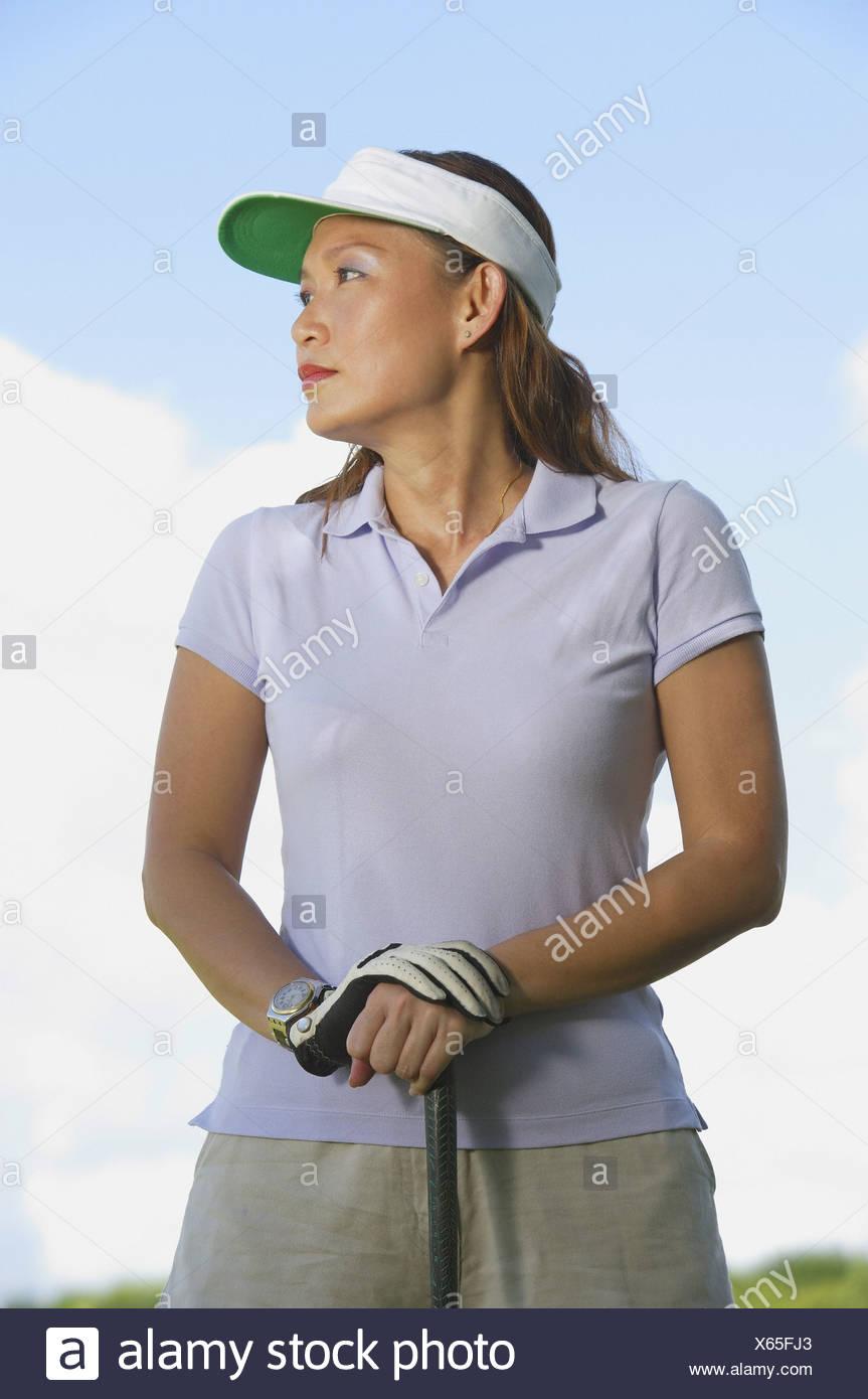 17196aa0 Woman wearing sun visor, leaning on golf club, looking away Stock ...