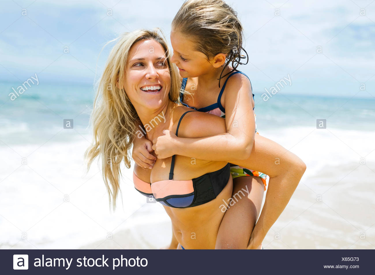 Mother carrying daughter (6-7) on back - Stock Image