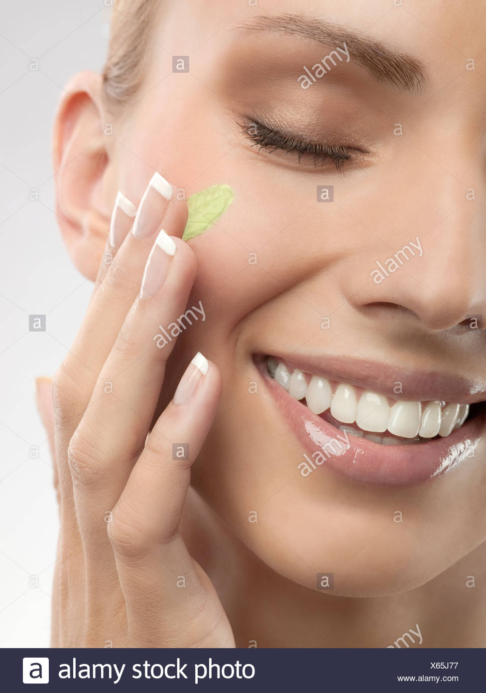 A woman putting green cream on her face - Stock Image
