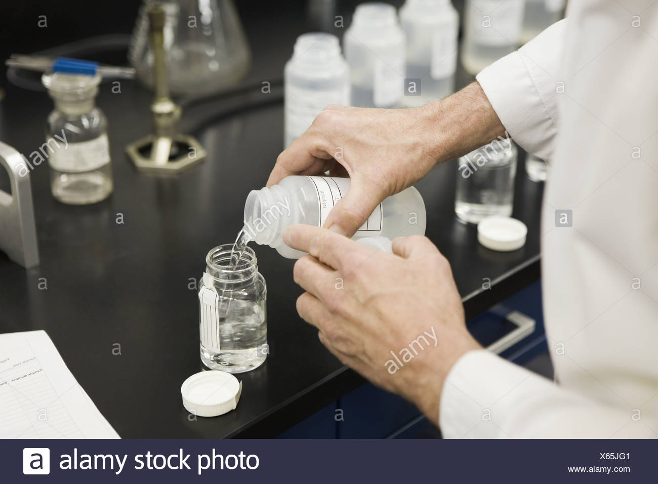 Mid section view of a scientist doing water testing experiment using defined substrate technology - Stock Image