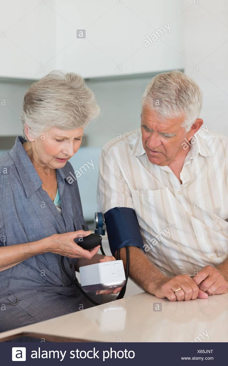 Senior woman checking her husbands blood pressure - Stock Image