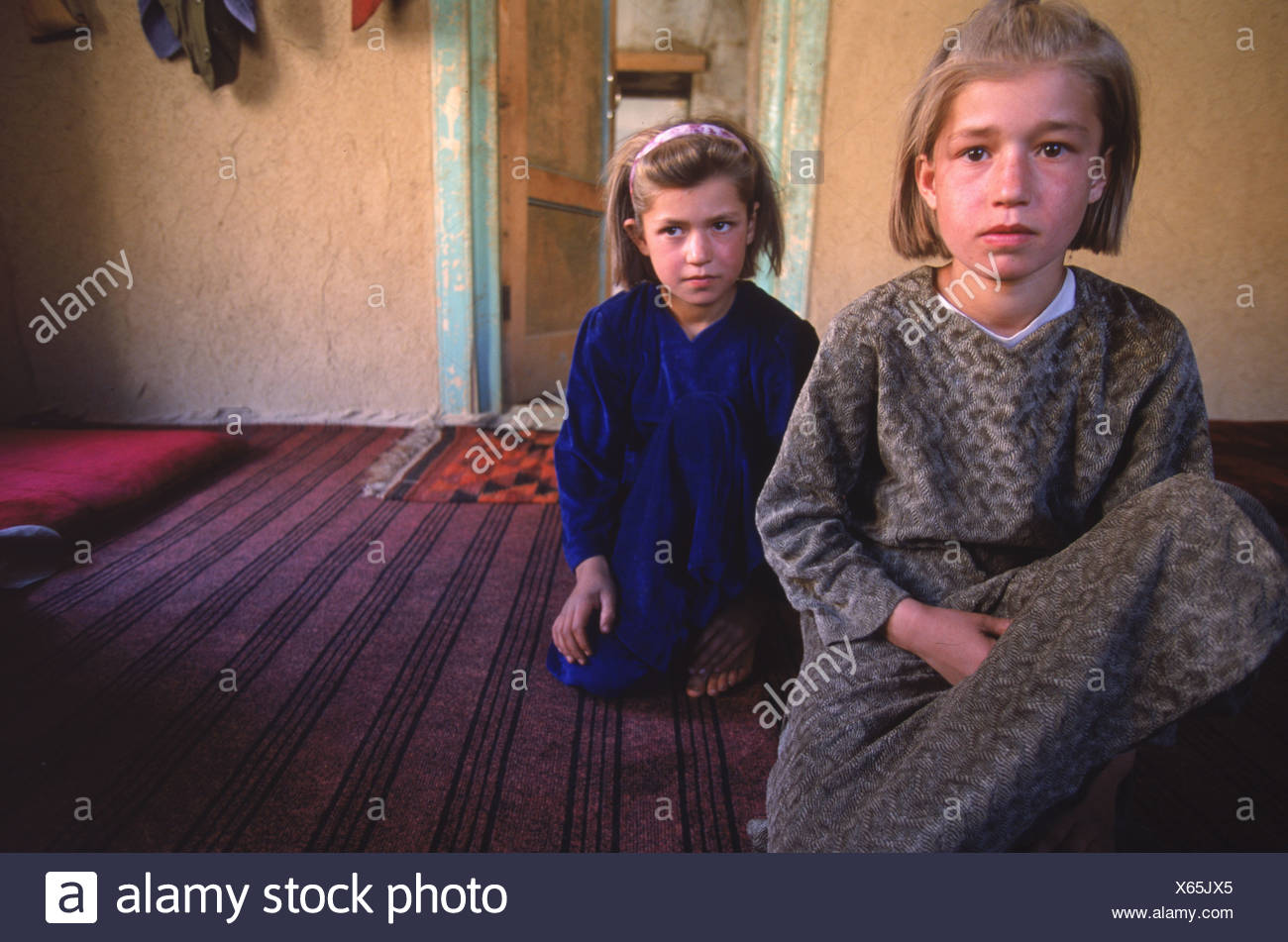Two girls sit in a guest room on a farm in the Panjshir Valley Hindu Kush - Stock Image