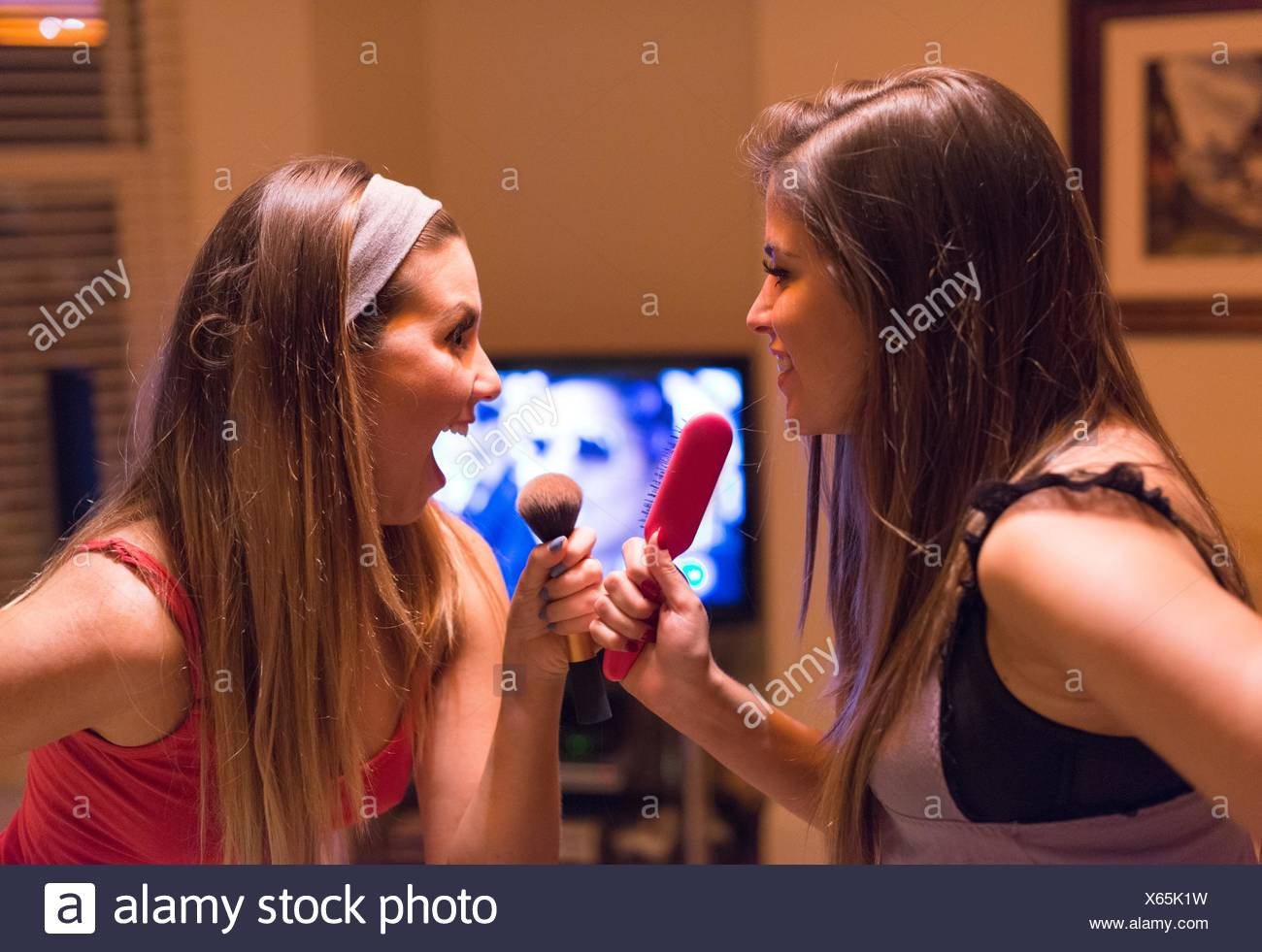 Two young women, singing into hair and make-up brushes - Stock Image