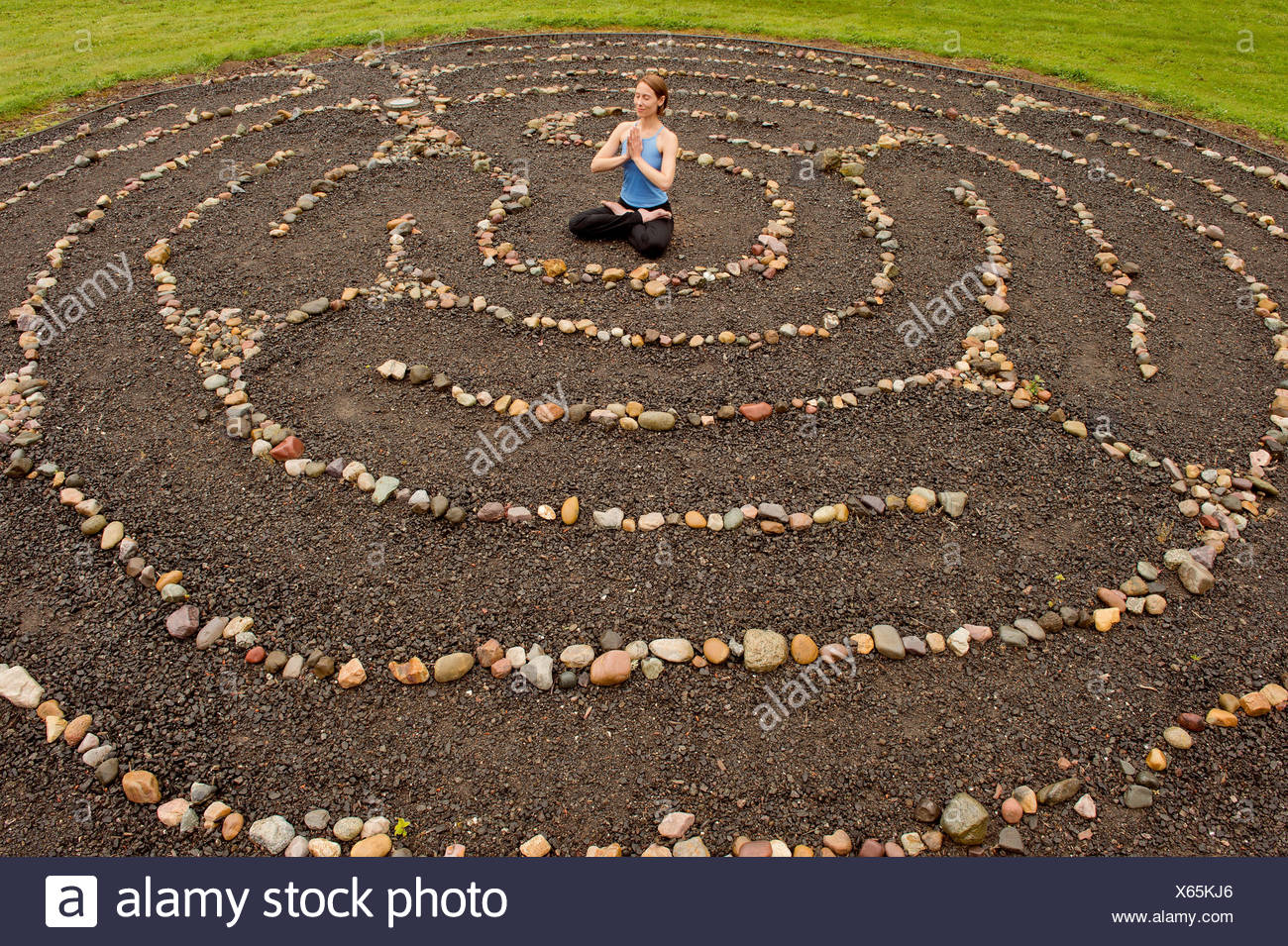 Woman meditating in stone labyrinth - Stock Image