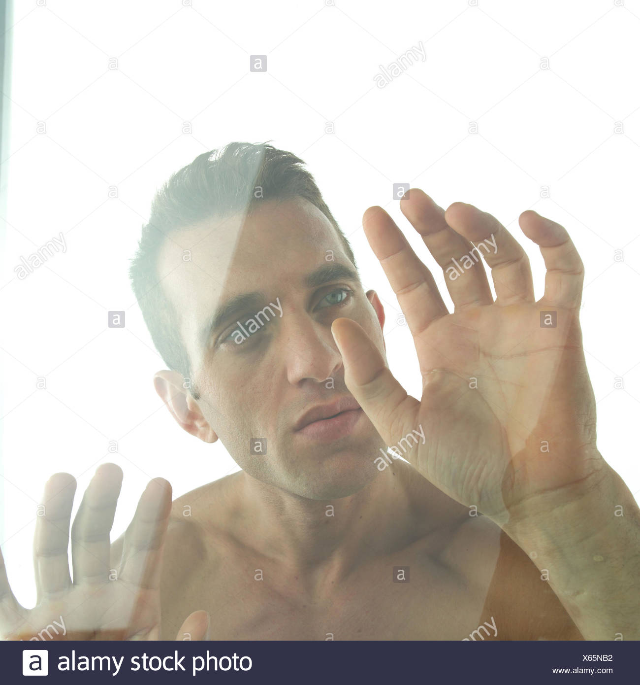 Man, free upper part of the body, gesture, slice, portrait, very close, expression, seriously, thoughtful, thoughtfulness, seriousness, uncertainly, insecurity, isolates, isolation, hand, palm, windowpane, feel, feel, touch, quarantine, confuses, confusion, disorientated, disorientation - Stock Image
