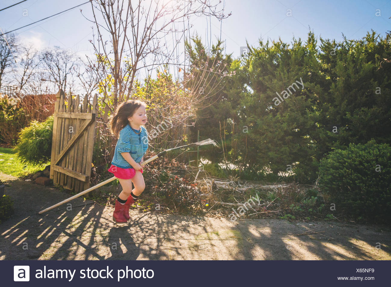 Young girl riding rake through yard like it's a horse - Stock Image