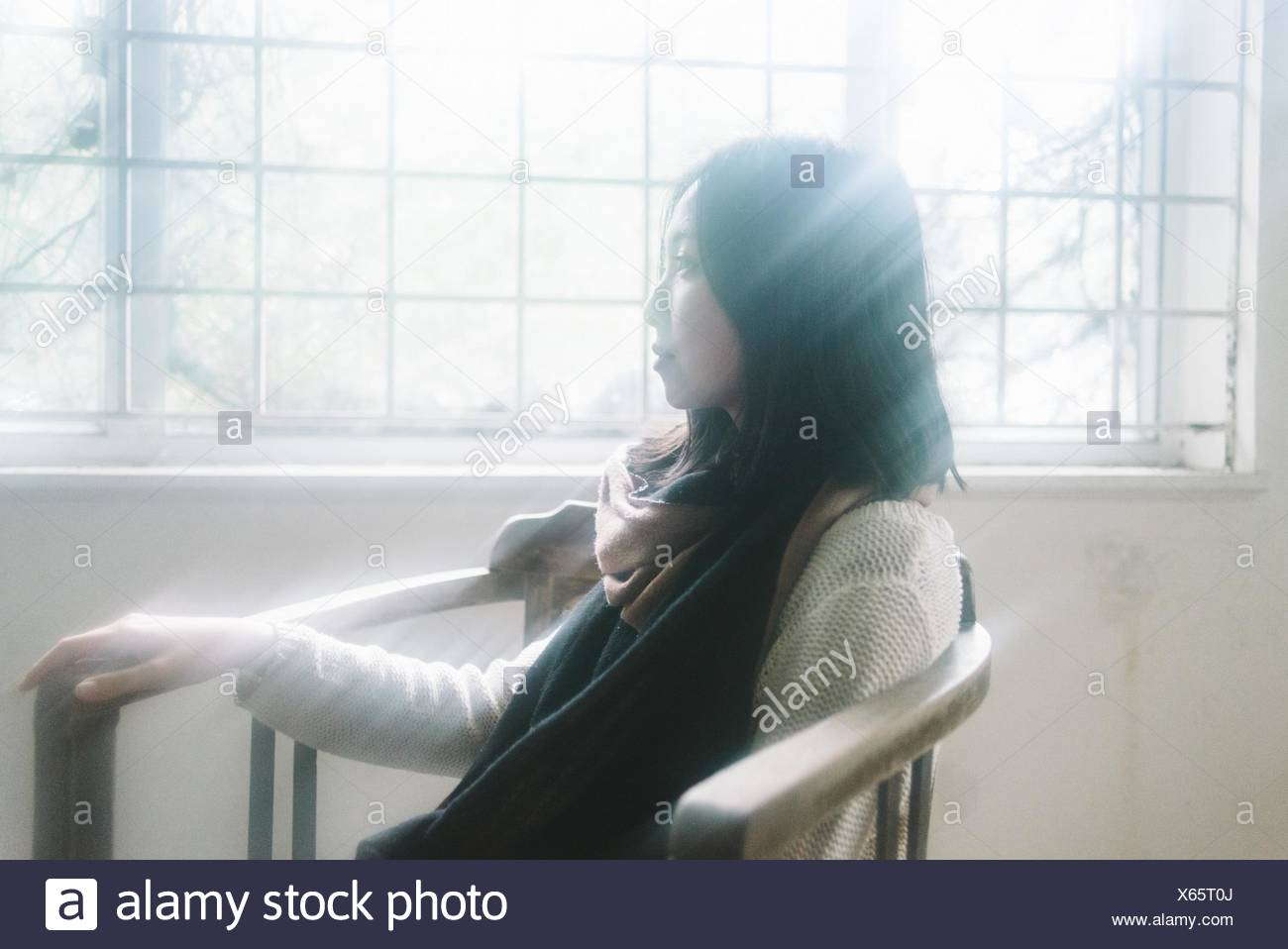Young Woman Sitting On Chair Against Window At Home - Stock Image