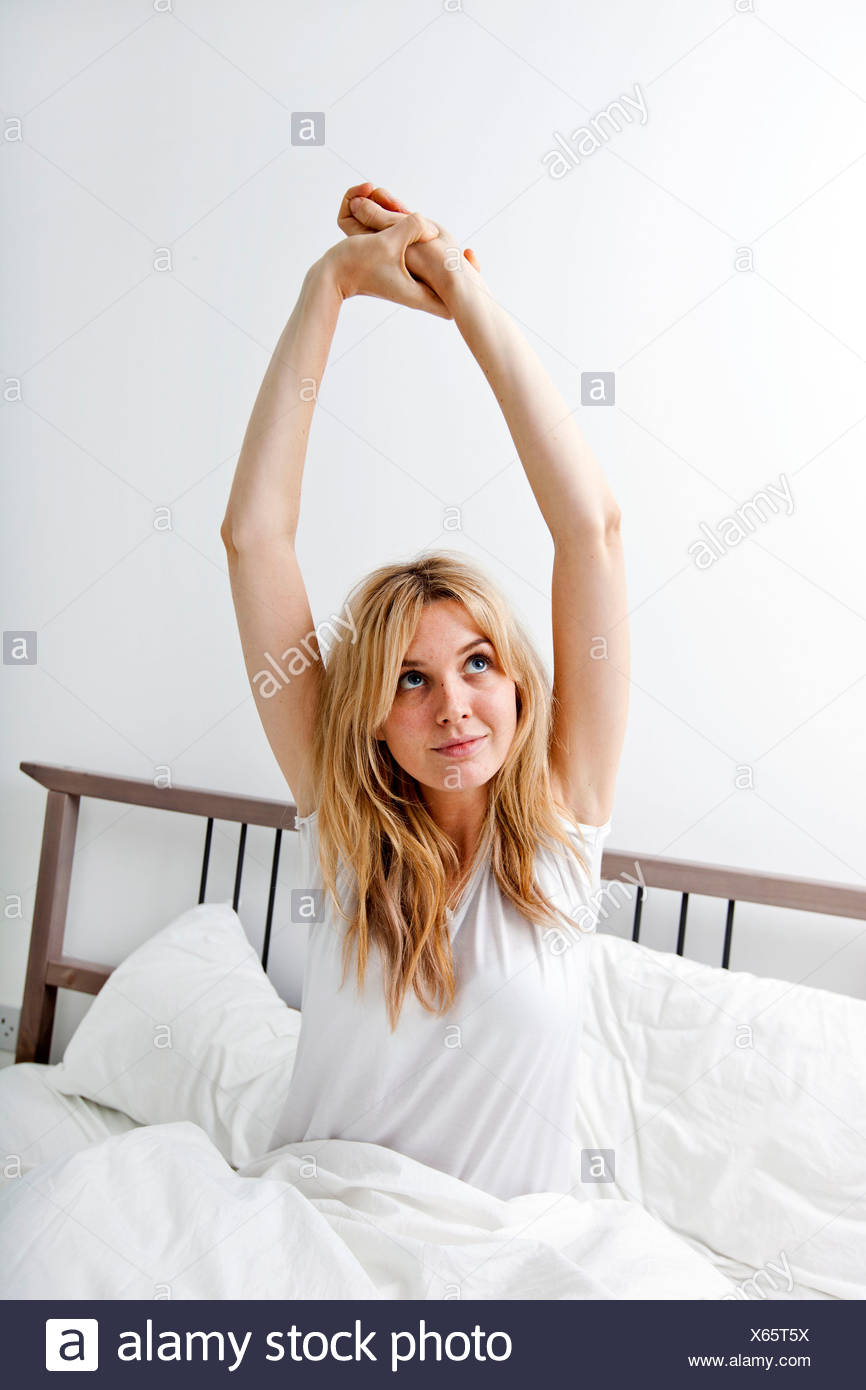 Young woman stretching in bed - Stock Image