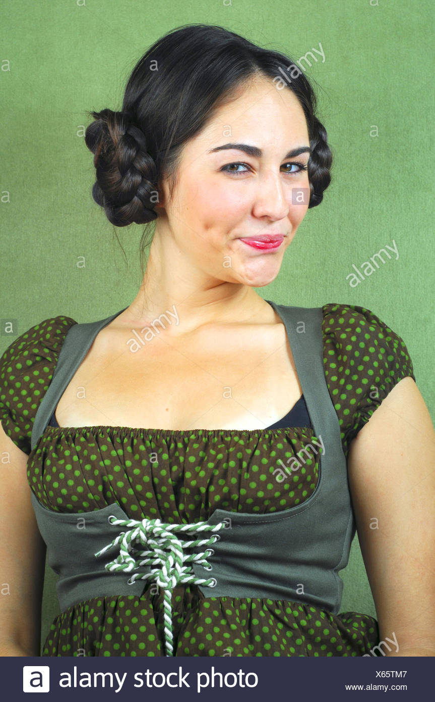 rougishly young darkhaired woman in dirndl looking at the camera - Stock Image
