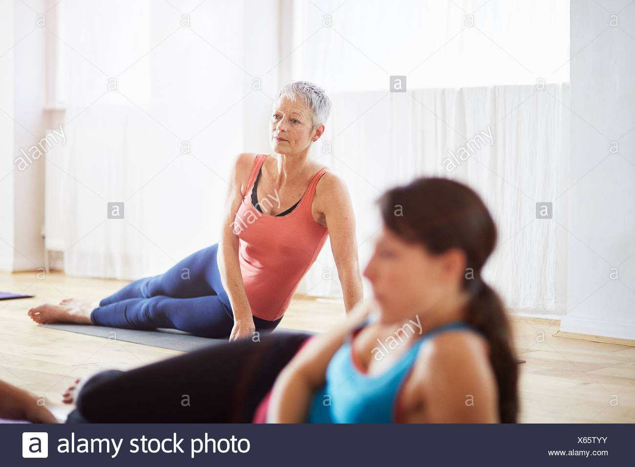 Two women lying on side in pilates class - Stock Image