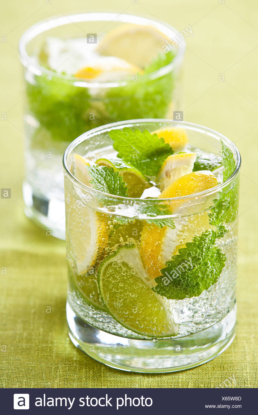 Cold fresh lemonade with lemon and lime on green background Stock Photo