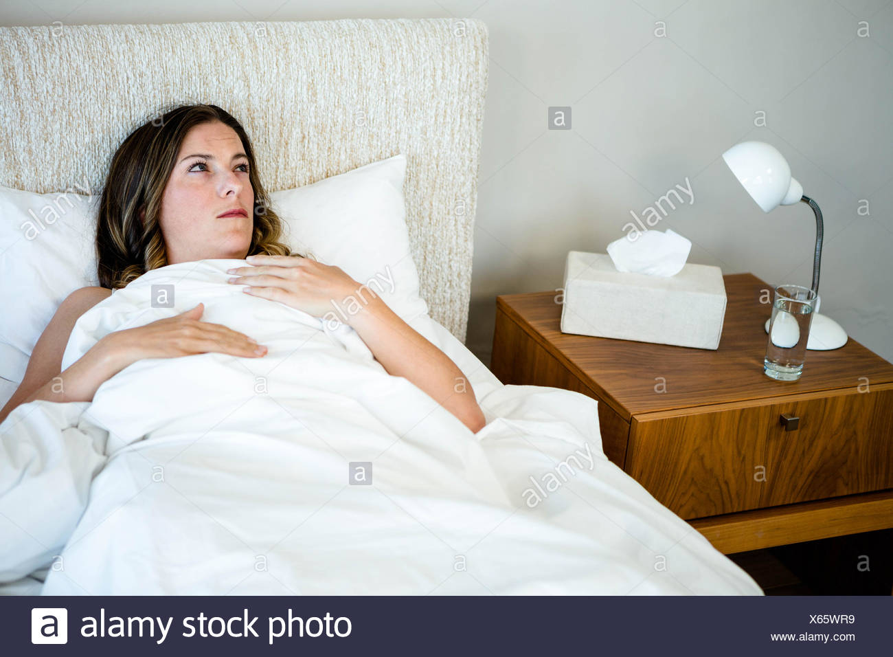 sick woman lying in bed looking unwell - Stock Image