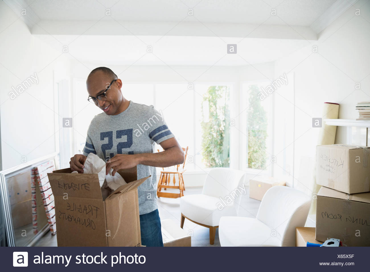 Man packing moving box in living room - Stock Image