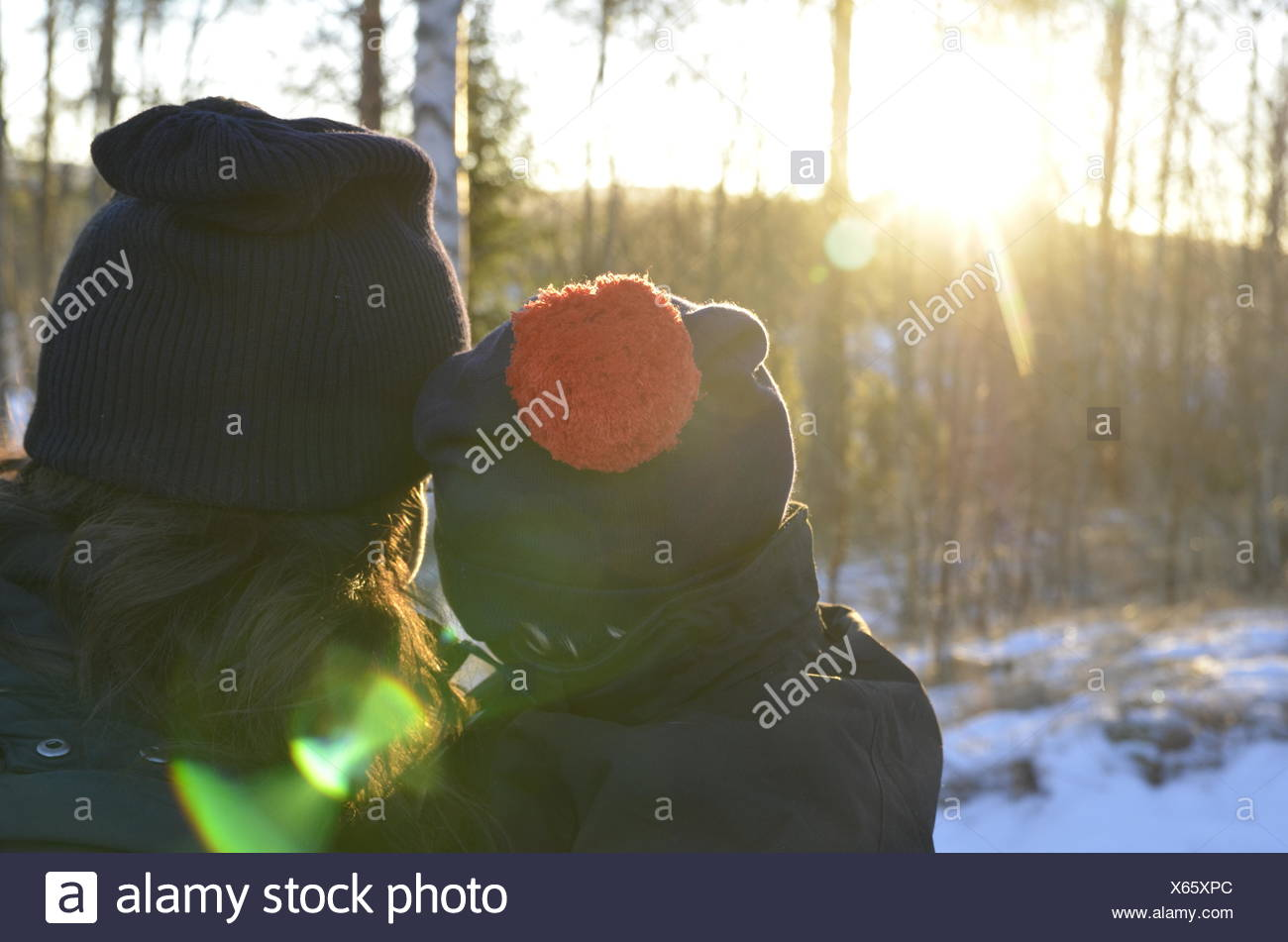 Rear View Of Mother And Child Against Trees During Winter - Stock Image