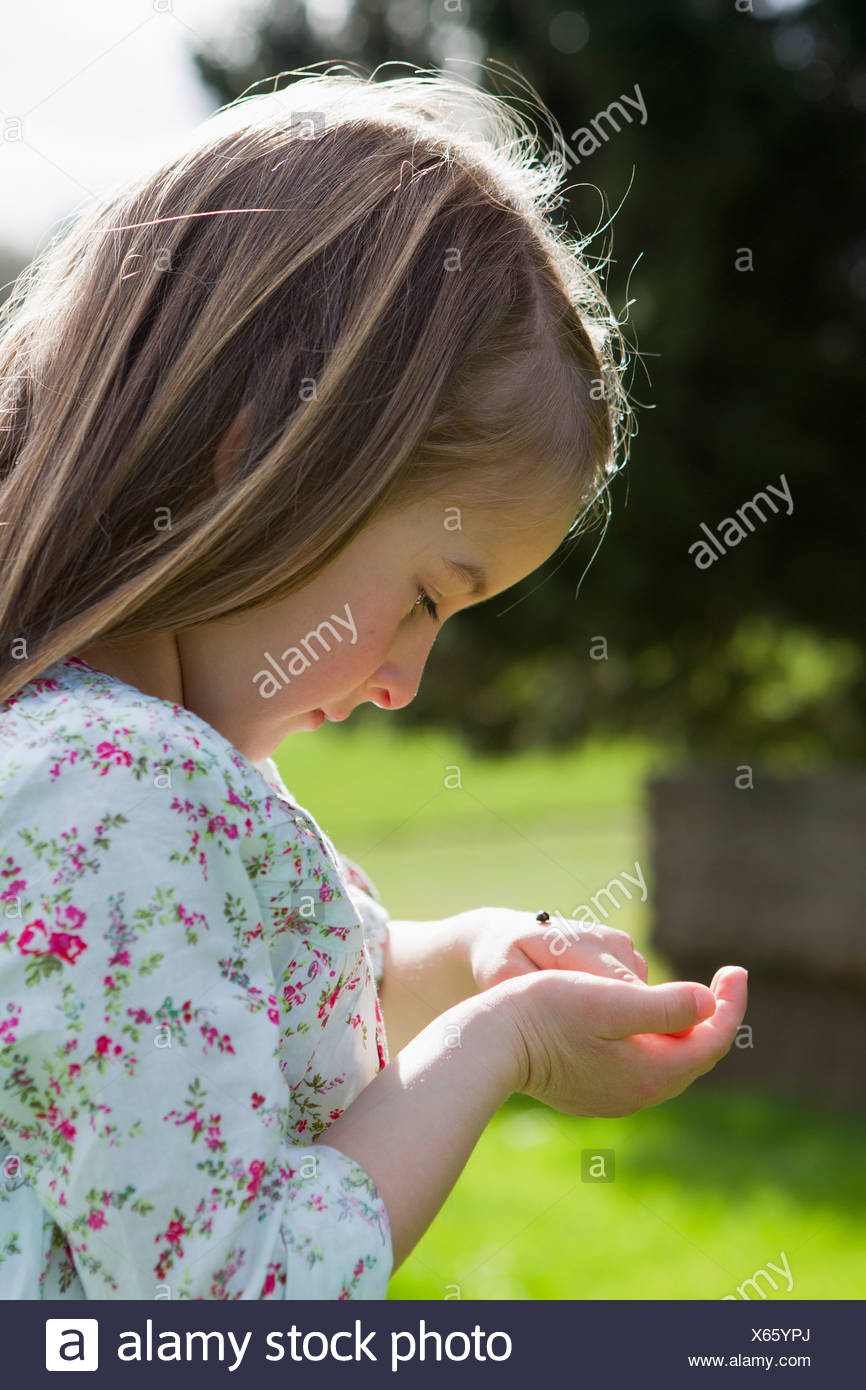 Girl examining insect on hand outdoors - Stock Image