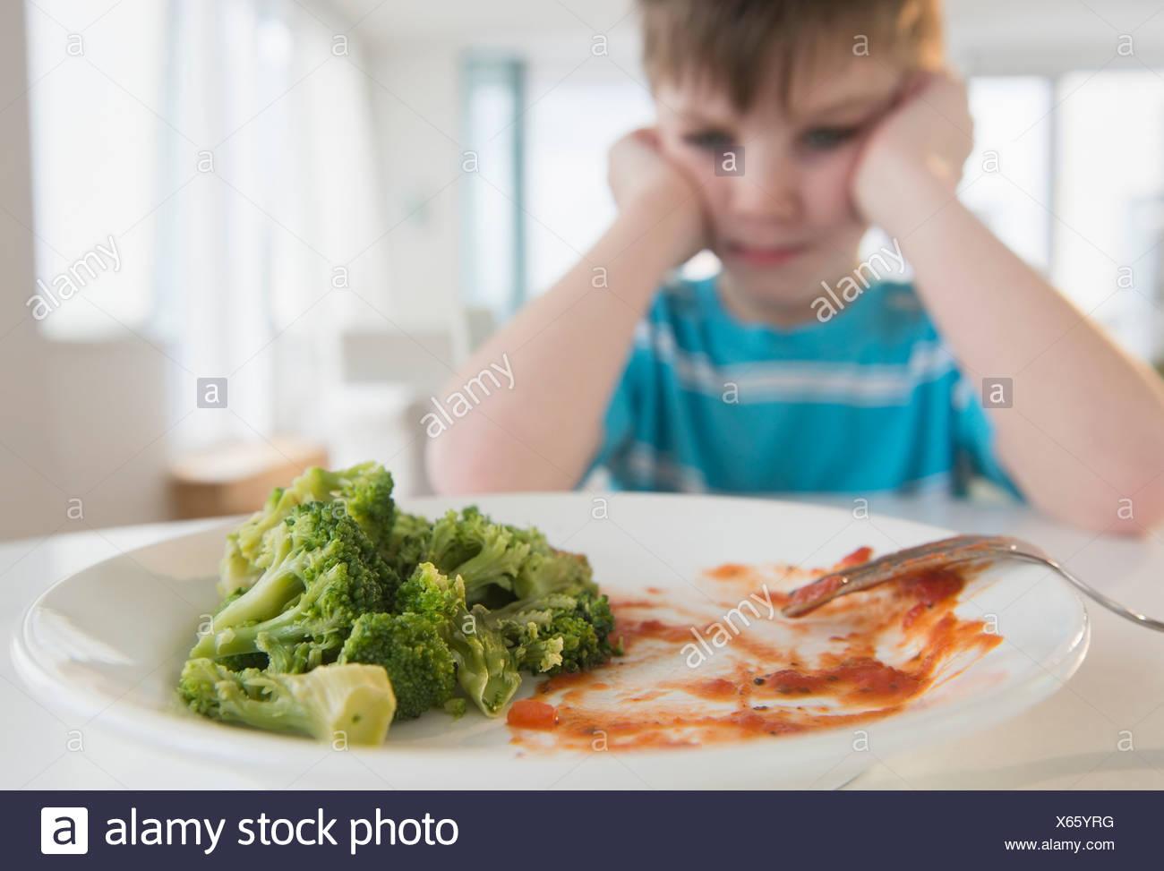 Portrait of boy (4-5) annoyed to eat broccoli - Stock Image