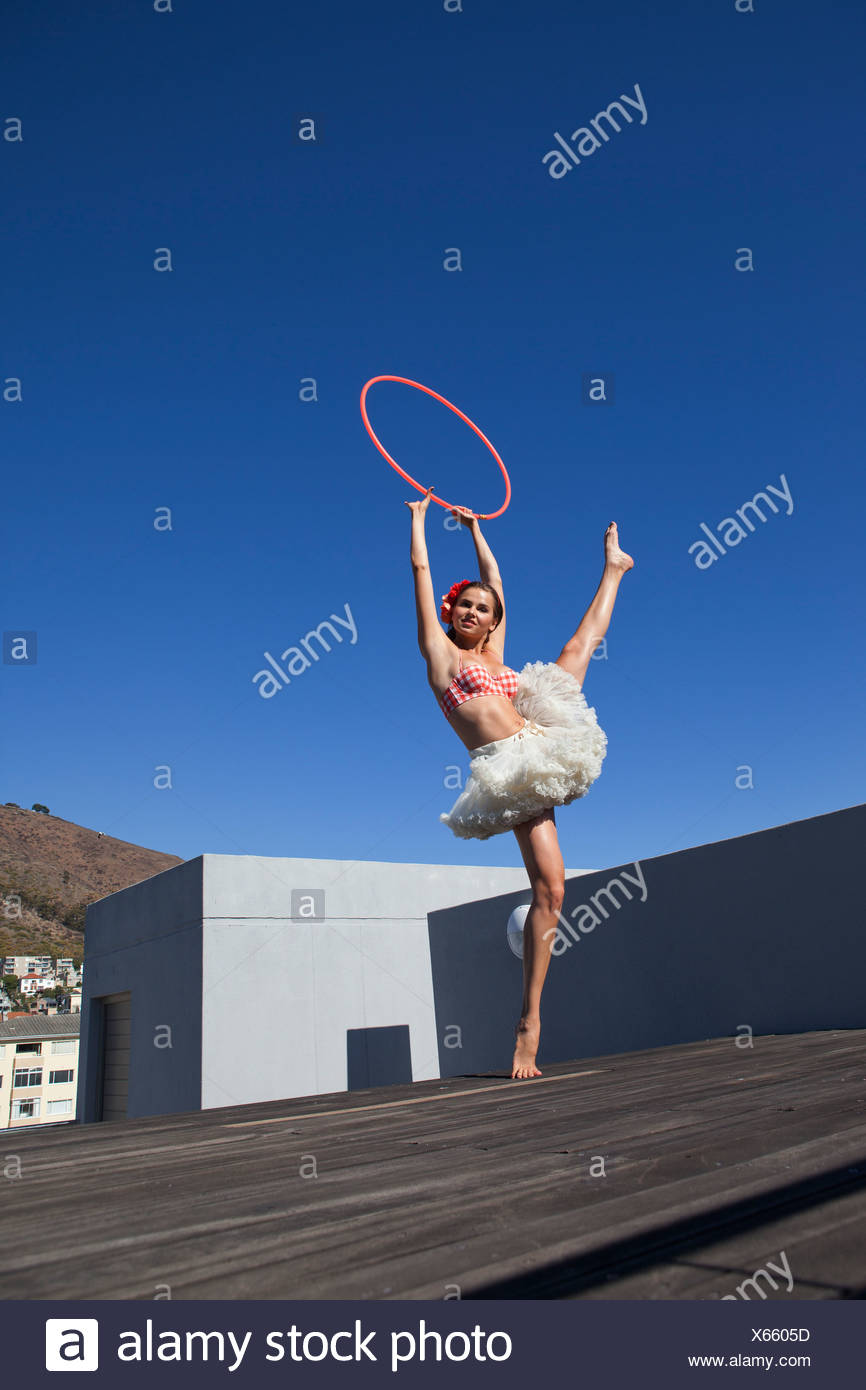 Woman in tutu dancing with hula hoop - Stock Image