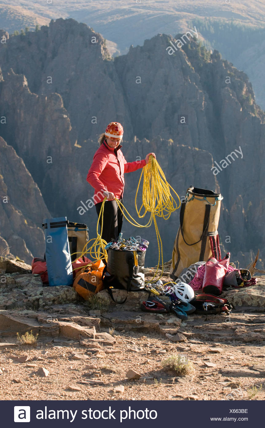 A woman coiling a climbing rope next to multiple bags of gear in the mountains of Crawford, Colorado. - Stock Image