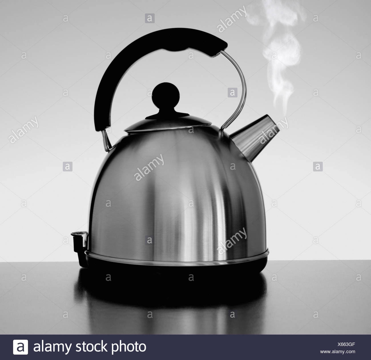 Tea kettle with steam indoors - Stock Image