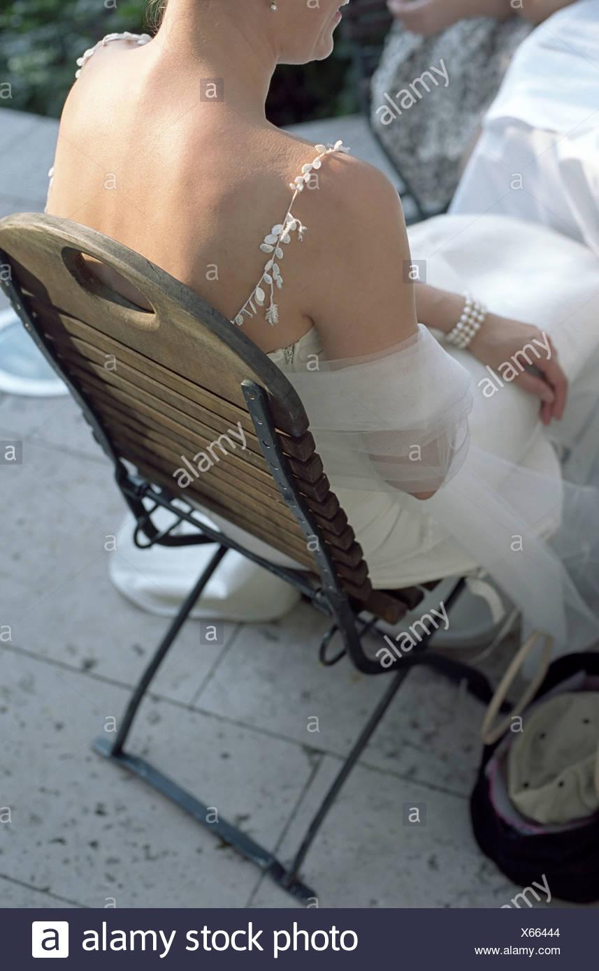 Bride sitting on a wooden Chair - Garden - Wedding Stock Photo