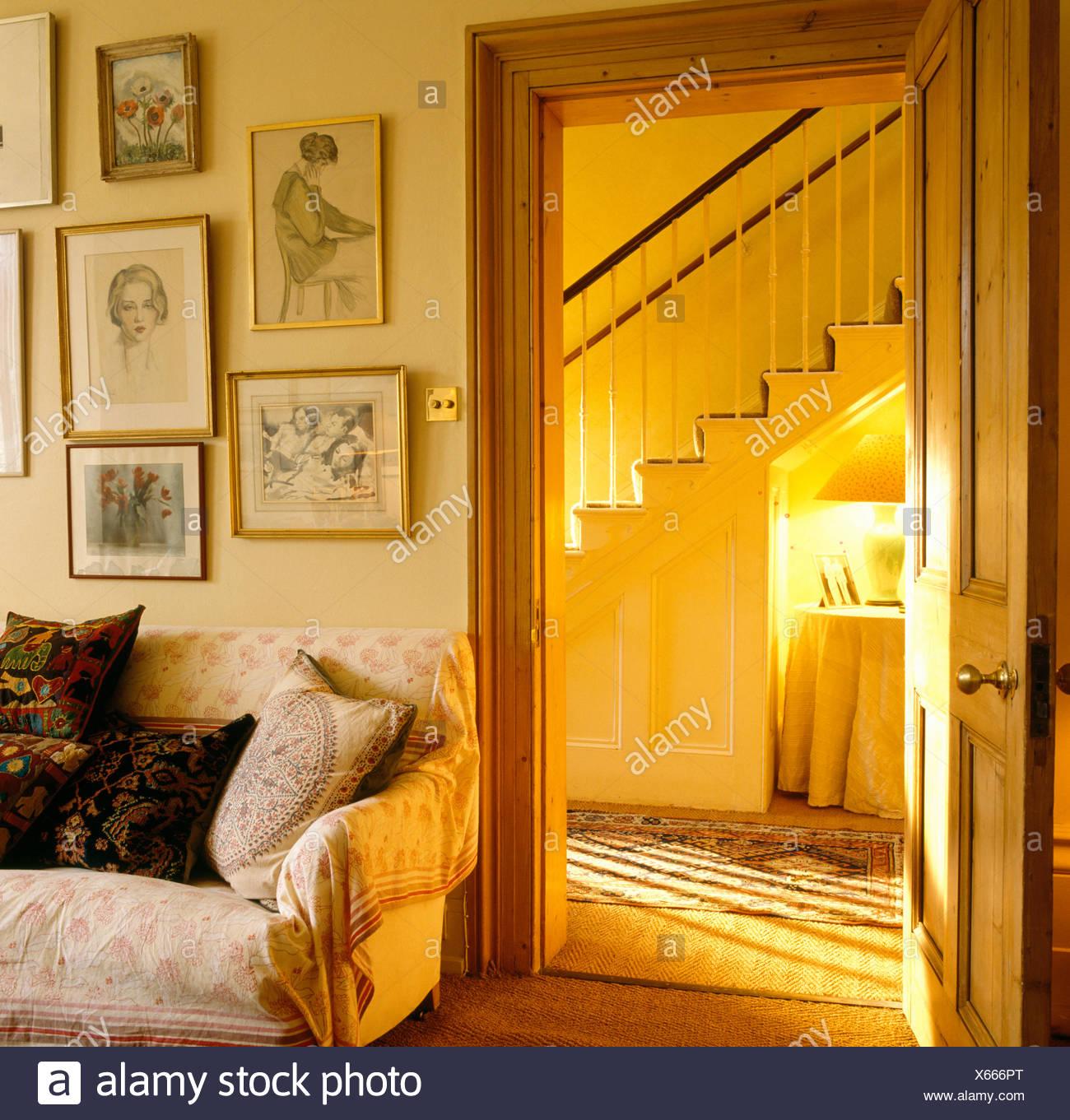 Eighties living room with framed drawings above sofa beside open door to hall - Stock Image