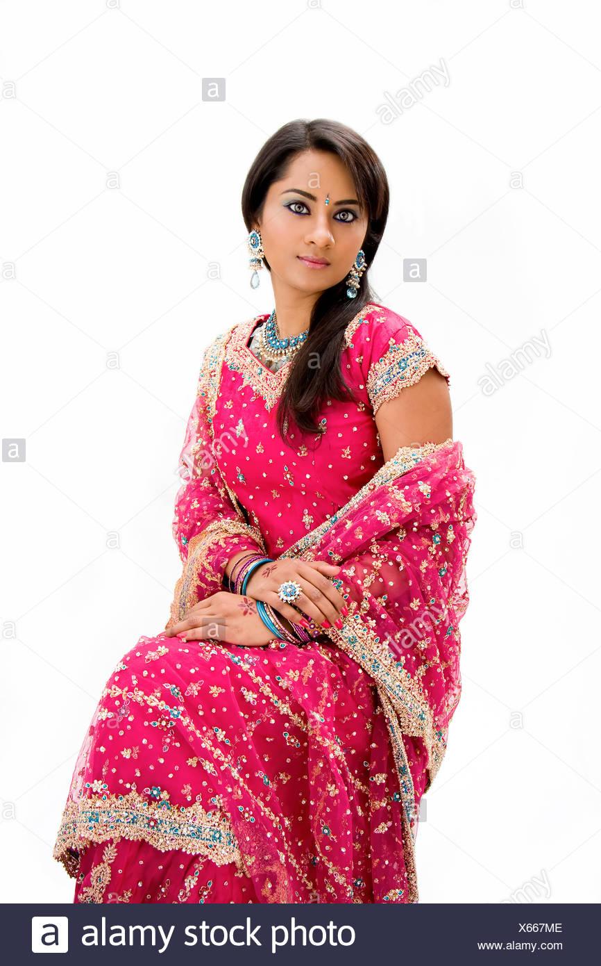 Beautiful Bangali bride in colorful dress sitting, isolated - Stock Image