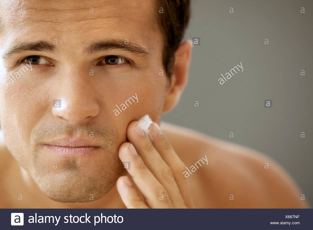Close-up of young man applying shaving cream - Stock Image