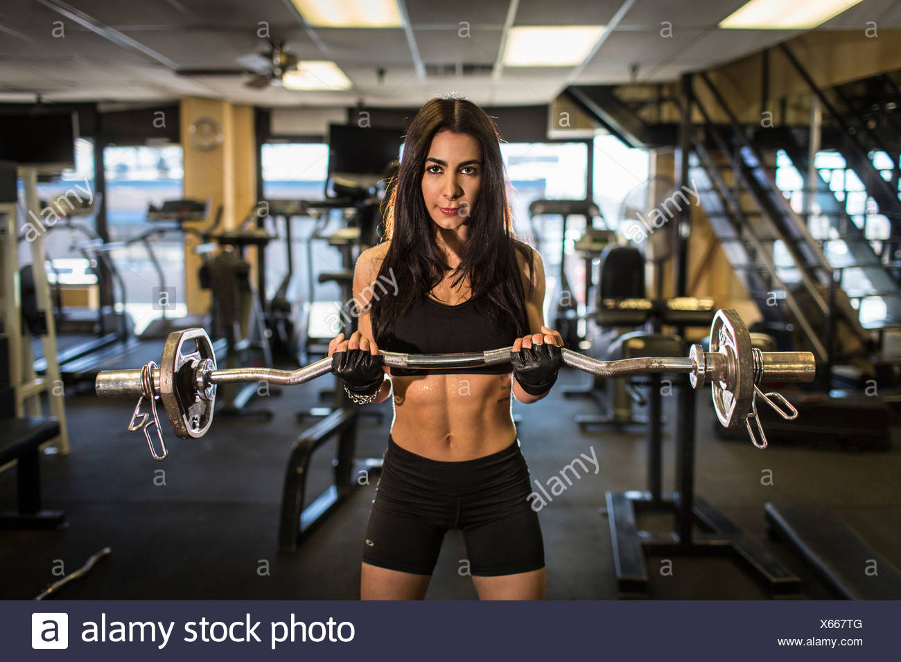 Portrait of mid adult woman weightlifting in gym Stock Photo