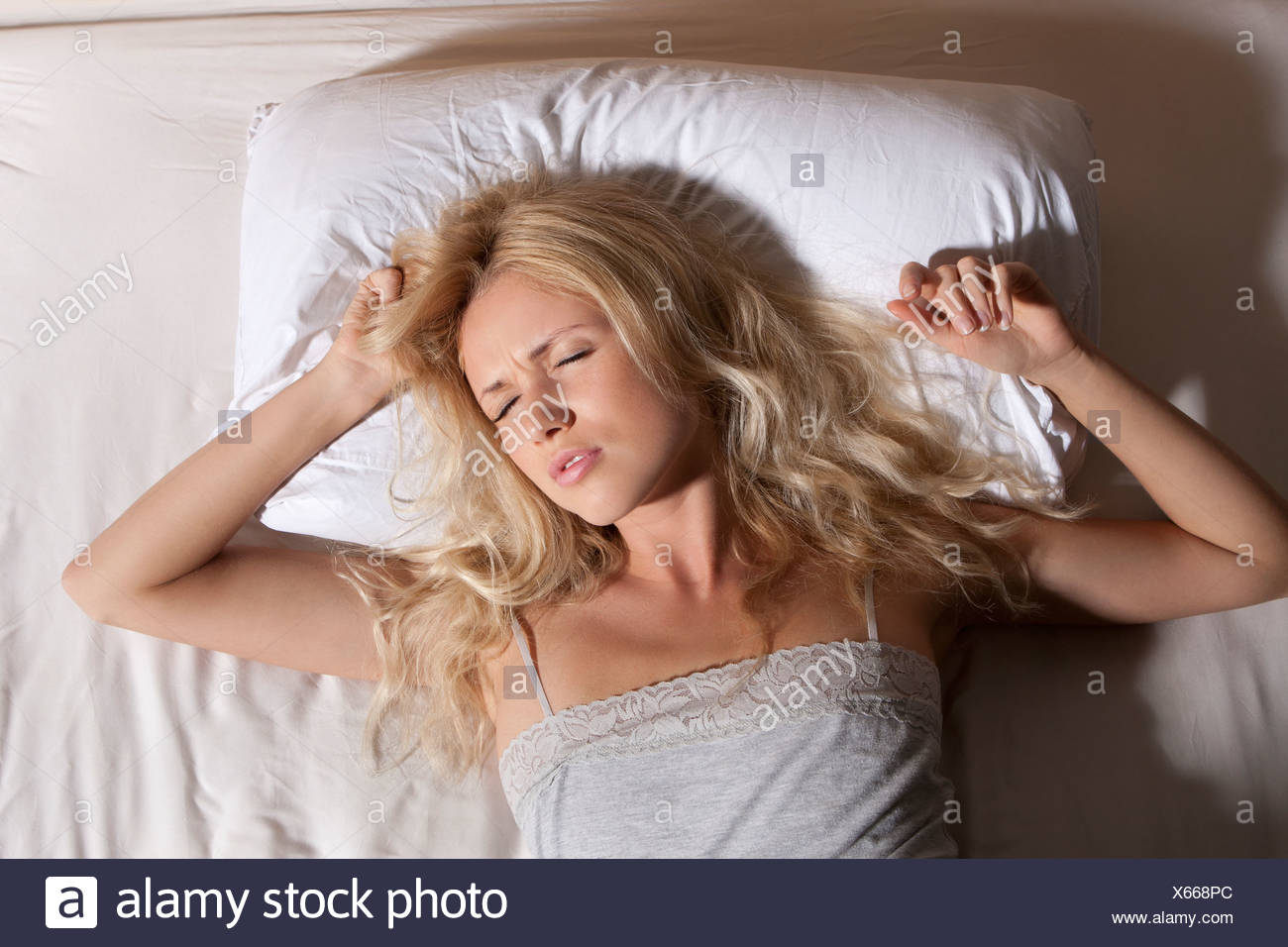 Woman sleeping fitfully in bed - Stock Image