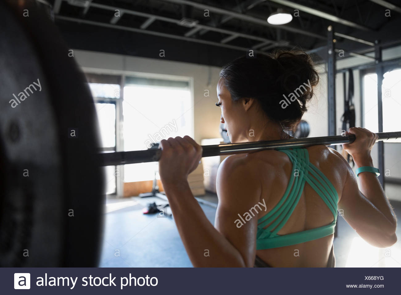 Woman weightlifting with barbell at gym Stock Photo