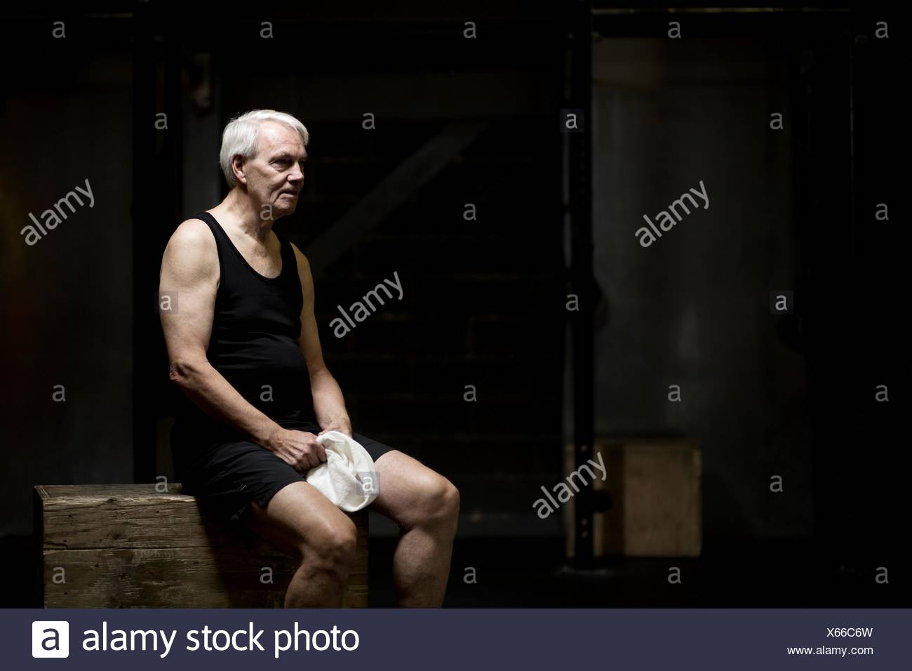 Senior man sitting resting in dark gym - Stock Image