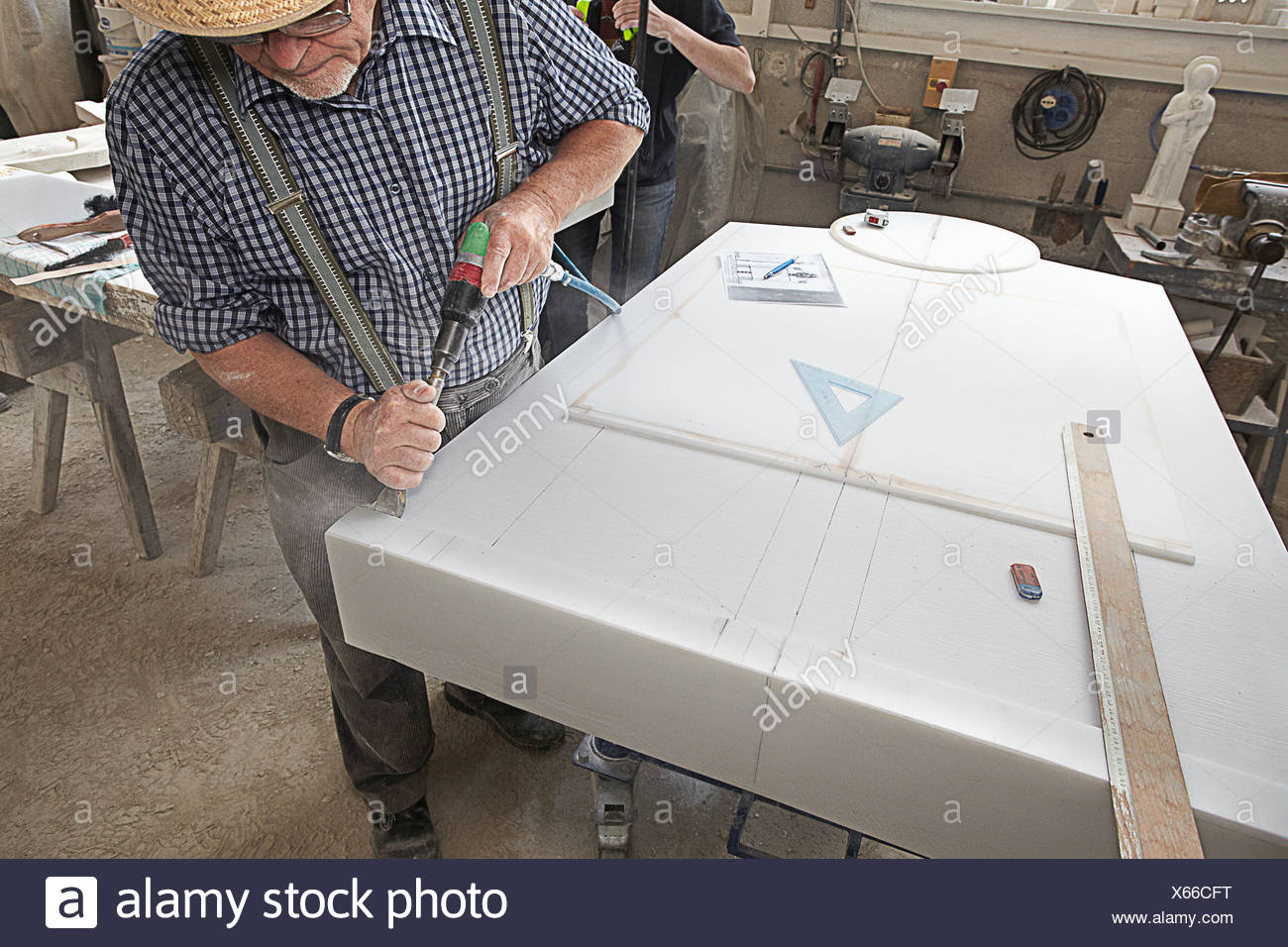 Worker chiseling slab of stone - Stock Image