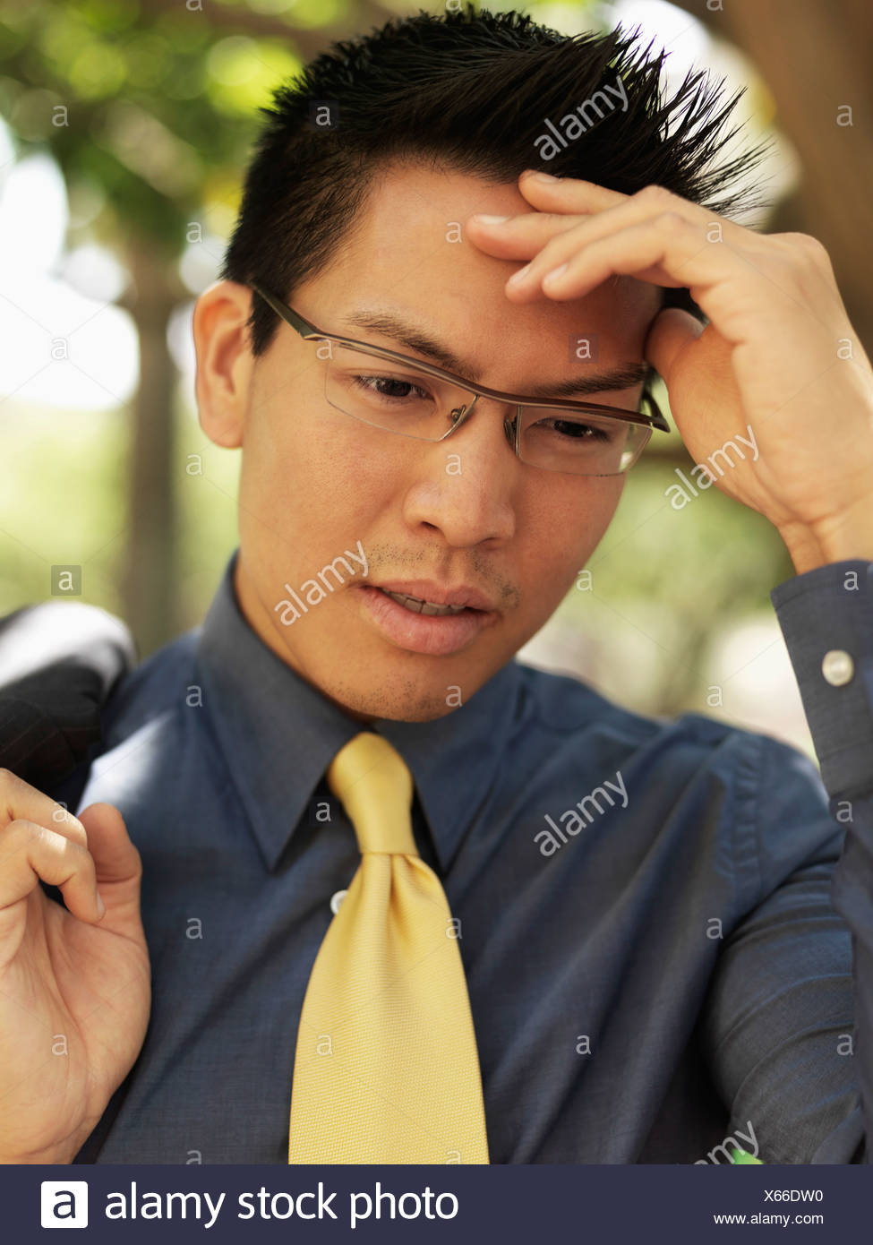 A businessman holding his forehead and grimacing - Stock Image
