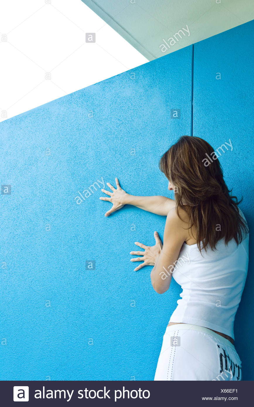 Woman holding on to wall, side view - Stock Image